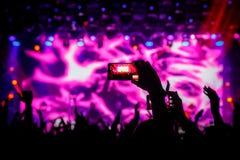 Smartphone ? disposition ? un concert, lumi?re pourpre d'?tape image libre de droits