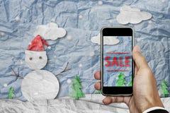 Smartphone a disposizione con il ` di VENDITA del ` sullo schermo, con carta sgualcita ha tagliato il pupazzo di neve nell'invern Fotografie Stock Libere da Diritti
