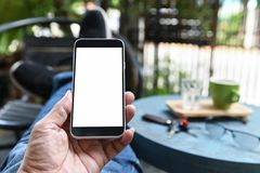 Smartphone a disposizione, parte posteriore è caffè sulla tavola e sulla gamba sulla sedia fotografie stock
