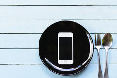 Smartphone do conceito na placa preta e na colher com a forquilha no fundo azul Fotografia de Stock