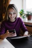 Smartphone do desdobramento da jovem mulher imagens de stock