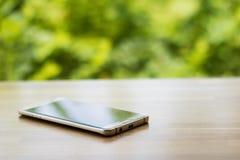 Smartphone do ouro na tabela de madeira com backgroun verde obscuro da árvore Imagens de Stock