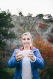 Smartphone do uso do caminhante da mulher que toma a foto no fundo da montanha e da floresta imagens de stock
