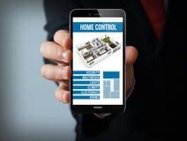Smartphone domestico astuto online dell'uomo d'affari di controllo immagini stock libere da diritti