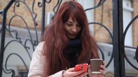 Smartphone dziewczyna używa app na telefonie pije kawowy ono uśmiecha się outdoors w mieście zbiory