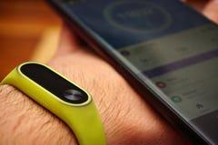 Smartphone e braccialetto dell'inseguitore di attività di forma fisica sulla fine del polso sulla vista fotografia stock libera da diritti