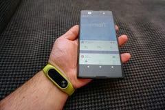 Smartphone e braccialetto dell'inseguitore di attività di forma fisica sulla fine del polso sulla vista immagine stock