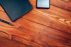 Smartphone e caderno na tabela de madeira Imagem de Stock Royalty Free