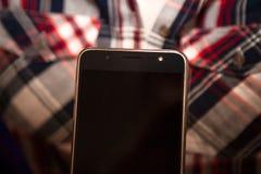 Smartphone e camicia femminile a quadretti Immagine Stock Libera da Diritti