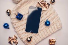 Smartphone e chapéu do inverno no fundo branco Imagem de Stock Royalty Free