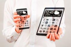 Smartphone e compressa con lo schermo trasparente in mani umane. Immagini Stock