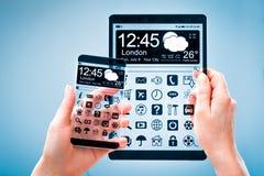 Smartphone e compressa con lo schermo trasparente in mani umane Immagine Stock Libera da Diritti