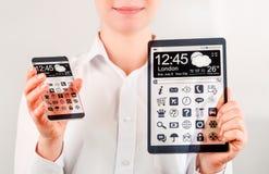 Smartphone e compressa con lo schermo trasparente in mani umane Fotografie Stock
