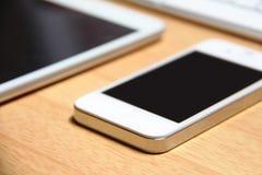 Smartphone e compressa sulla tavola Immagini Stock Libere da Diritti