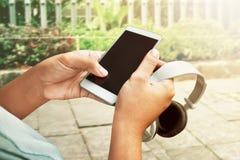 Smartphone e cuffie della tenuta fotografie stock libere da diritti