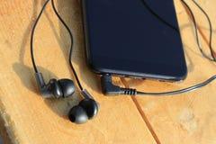 Smartphone e cuffie neri su un fondo marrone chiaro di legno immagini stock libere da diritti