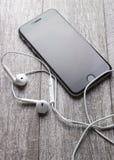 Smartphone e fones de ouvido na tabela de madeira Foto de Stock