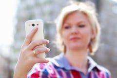 Smartphone e lettura biondi della tenuta della donna Fotografia Stock Libera da Diritti