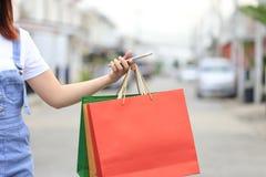 Smartphone e sacos de compras da terra arrendada da m?o da jovem mulher com posi??o no parque de estacionamento do carro imagens de stock royalty free