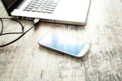Smartphone e un computer portatile su un desktop Fotografia Stock