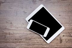 Smartphone e una compressa sui precedenti di legno Immagine Stock Libera da Diritti