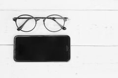 Smartphone e vetri di lettura fotografie stock