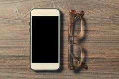 Smartphone e vetri di lettura su un bordo di legno anziano immagine stock