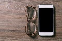 Smartphone e vidros de leitura em uma placa de madeira velha imagens de stock