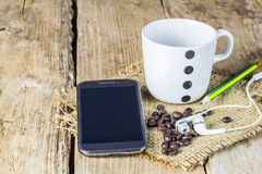 Smartphone, earphone,coffee beans and coffee mug on wooden table Stock Images