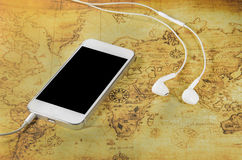 Smartphone and earphone on a old world map Stock Photos