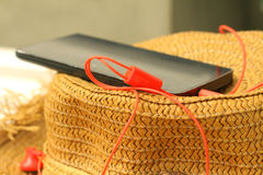 Smartphone with earphone, straw hats Royalty Free Stock Photos