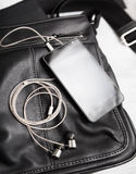 Smartphone with earphones on black leather Stock Photos