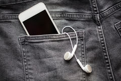 Smartphone and earphones in denim or jeans pocket Royalty Free Stock Image