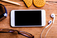 Smartphone, earphones, eyeglasses and smart watch on office desk Royalty Free Stock Image
