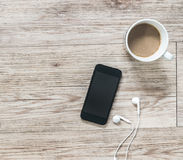 Smartphone, earphones, notebook and coffee on wooden background Stock Photos