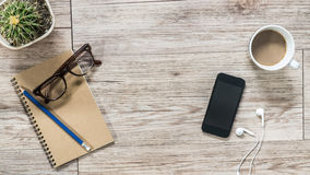 Smartphone, earphones, notebook and coffee on wooden background Royalty Free Stock Images