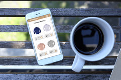Smartphone with ecommerce website screen and coffee cup. On wooden Royalty Free Stock Photos