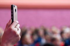 Smartphone in een vrouwelijke hand auditorium Vage roze achtergrond Foto of video op een mobiele telefoon Leef uitzending met de  royalty-vrije stock foto's
