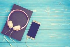 Smartphone, el nuevo auricular rosado moderno y el libro de la música en azul cortejan Imagenes de archivo