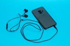 Smartphone em uma caixa cinzenta de matéria têxtil com fones de ouvido conectados em um fundo azul foto de stock