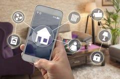 Smartphone em uma mão em uma sala de visitas imagens de stock