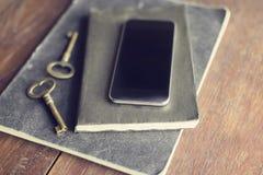 Smartphone en blanco con llaves del vintage y diarios en la tabla de madera Fotos de archivo