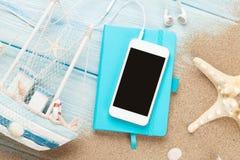 Smartphone en blocnote op overzees zand met zeester en stuk speelgoed boot Royalty-vrije Stock Fotografie