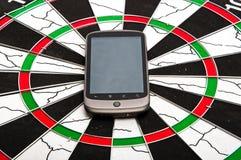 Smartphone en dartboard imagenes de archivo
