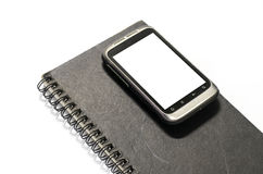 Smartphone en el cuaderno Imagenes de archivo
