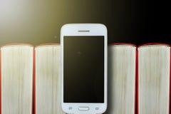 Smartphone en el fondo de libros Fondo oscuro, espacio de la copia Concepto: libros y artilugios electrónicos foto de archivo libre de regalías