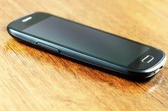 Smartphone en el tablero de madera Fotos de archivo libres de regalías