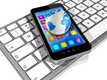 Smartphone en el teclado de ordenador y el globo del mundo Imagenes de archivo