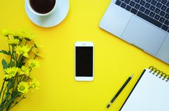 Smartphone en fondo amarillo con la nota, las flores, el café y el ordenador portátil foto de archivo