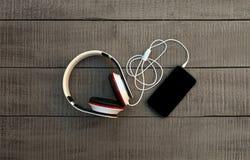 Smartphone en hoofdtelefoons op een houten achtergrond Luister aan musi stock fotografie